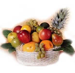 Arrangement of Apples, Grapes, Oranges and Pineapple in a cane basket.